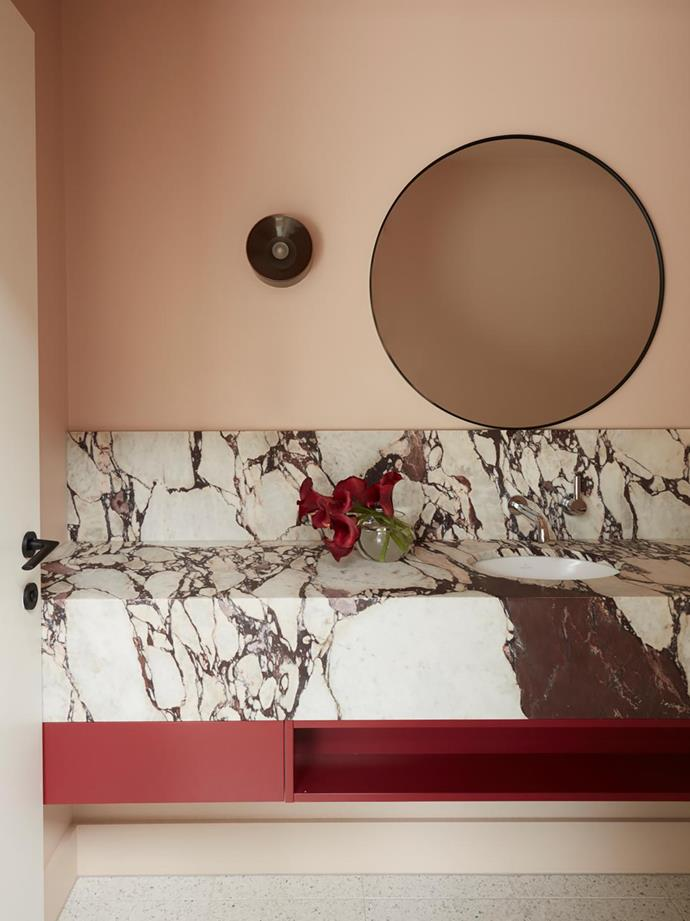 "This sophisticated powder room within a [revamped postwar bungalow](https://www.homestolove.com.au/postwar-bungalow-modern-renovation-21954|target=""_blank"") has been swathed in peach hues and features joinery designed by Siobhann Studio. The Calacatta Viola benchtop, CDK Stone. makes a beautiful statement."