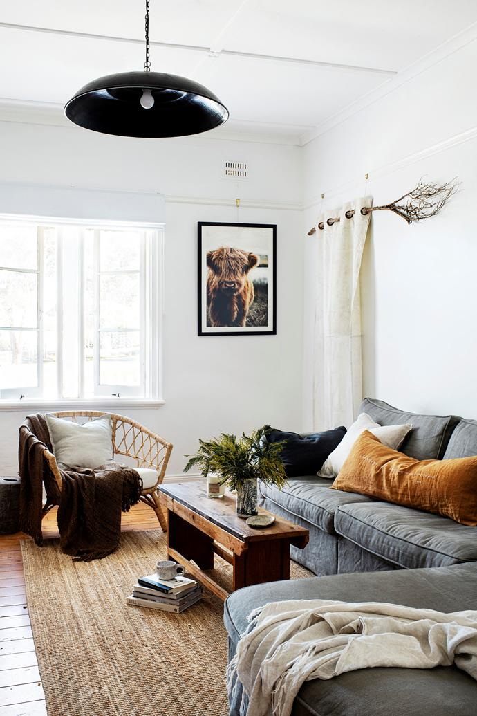 Photography by home owner Tim Bean adorns the wall, next to a Pony Rider recycled canvas hung on a branch foraged from the backyard. The coffee table is vintage.