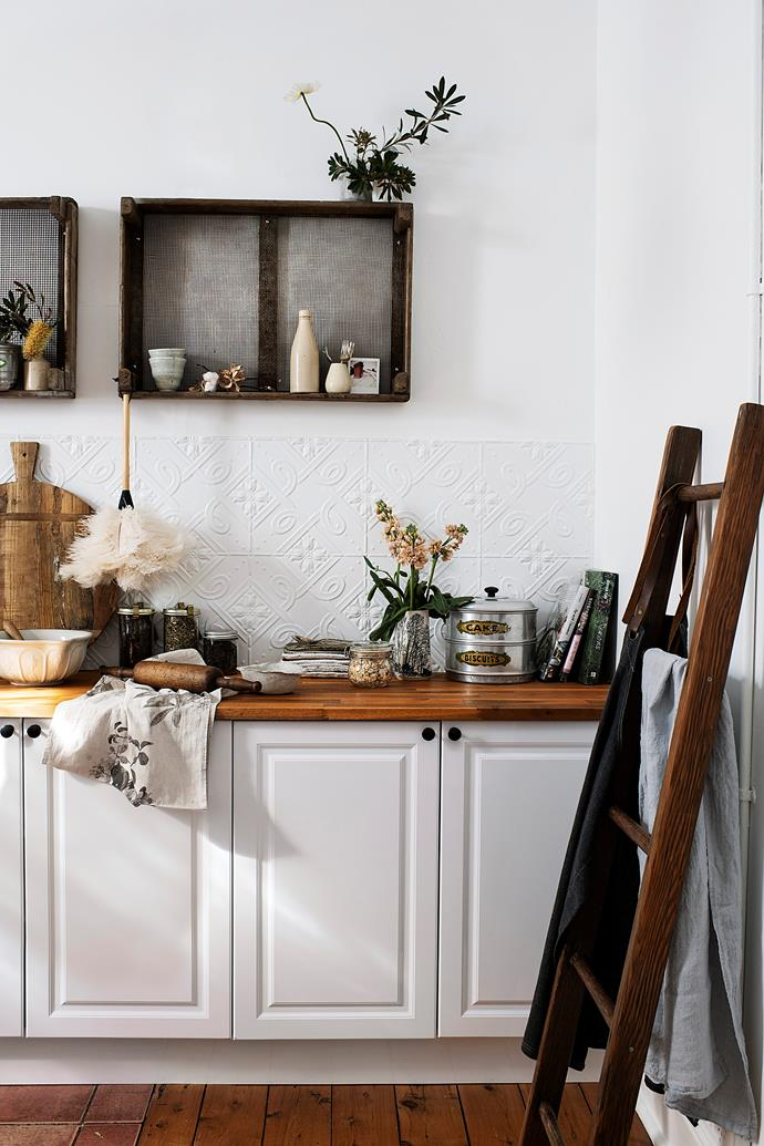 Old apple crates, found in an antiques shop years ago, hang on the wall. On the Kaboodle Heritage kitchen in gloss white, inherited from the previous owner, sits a bread board from Dirty Janes in Canberra, a vintage pudding basin and Scout + Bird cake tins.