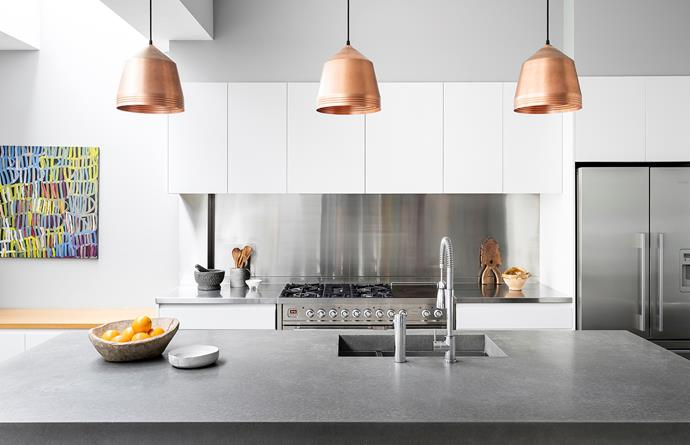 The island's polished-concrete bench is paired with stainless steel for the wall-side bench and splashback. Ilve 1200 cooker. Fisher & Paykel french-door fridge.