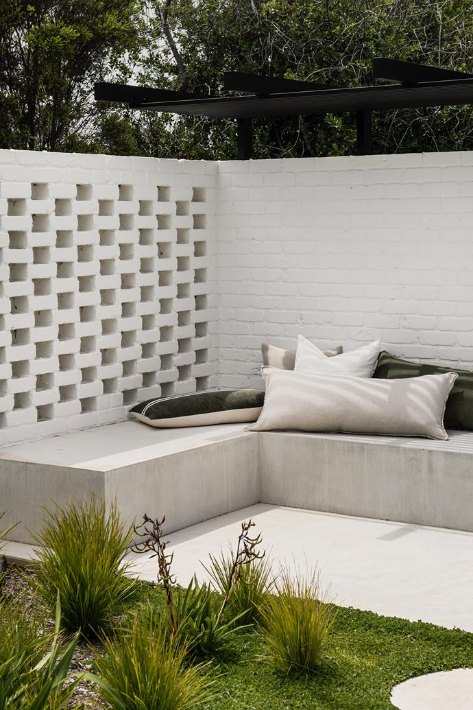 The minimalist garden of hardy grasses and succulents, created by JRLD Design + Landscape, is in tune with the tempestuous conditions the coastal environs can deliver. The custom bench seat in raw concrete sports a selection of cushions from Coastal Living.