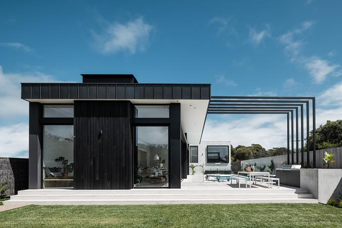 """The clients are regular entertainers so the design needed to integrate a private retreat at the front of the residence with a generous entertaining space at the rear,"" says Miriam Fanning. The home's dark exterior is striking against the coastal backdrop. 'Linear' dining table and benches from Tait."