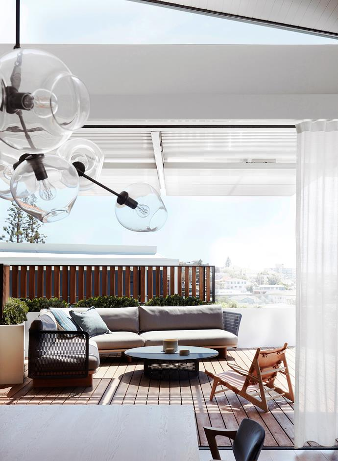 The front terrace is a relaxed extension of the living area where Kettal 'Mesh' loungers and coffee table in Indigo await with the 'Hunting' oak and leather chair from Great Dane. Lindsey Adelman 'Branching Bubble 9' pendant light.