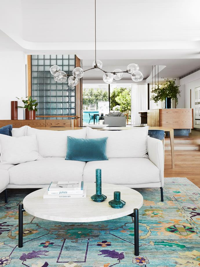 The living room is cool and serene with a Moroso 'Gentry' sofa from Hub on a silk and wool rug from Robyn Cosgrove. Coffee table from Spence & Lyda. Lindsey Adelman 'Branching Bubble 9' pendant light.