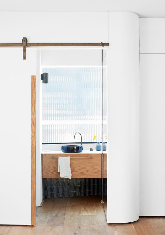 The powder room has a handmade basin by Lindsey Wherrett glazed to match the rich indigo tiles. Angled picture window in Broadline glass. Brodware 'City Stik' mixer in weathered brass from Candana. Soap dish from Oliver Thom. Society Limonta 'Lipe' hand towel from Ondene.