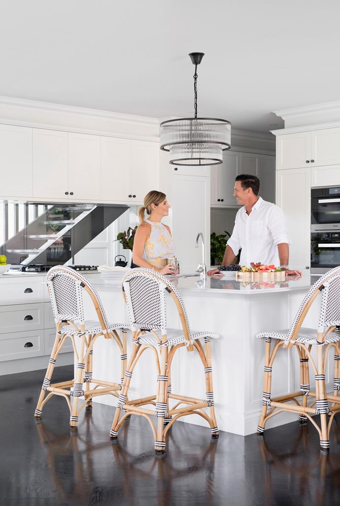 """A deep square island topped in Carrara marble from Precision Stone Services sees plenty of action in this busy household of six. """"It's where we all gravitate,"""" says Justine, pictured with Matt, of the bench teamed with chic stools from Provincial Home Living. """"Because it's so big, there's plenty of room for the kids to do their homework at the bench and we can chat while I'm making dinner or snacks."""" Opting for a modern yet timeless Shaker- style look, the couple chose joinery by Cabinet Fit that was colour matched to the walls in Dulux Lexicon Quarter, with pewter hardware coordinating with a pendant from Beacon Lighting. A glass splashback was an inspired choice. """"It allows us to see through to the front door and stairs, which is really handy and makes the kitchen feel even more like a central hub,"""" adds Justine. [Herringbone floors](https://www.homestolove.com.au/timber-herringbone-floors-20718