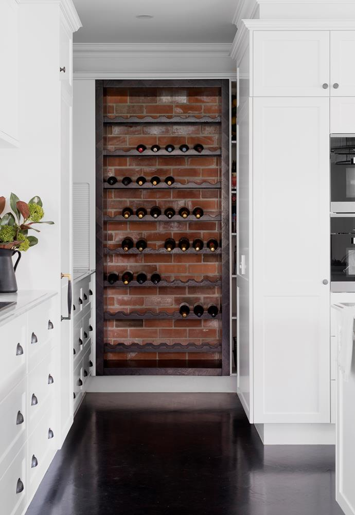 Recycled red bricks add a rustic backdrop to wine storage within the butler's pantry.