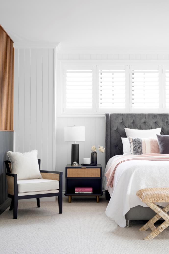 Cocooning and elegant, Matt and Justine's bedroom on the upper level is a luxurious retreat. A custom bedhead in Warwick Velvet Dolce Onyx fabric sets the tone for the moody palette, as do Coco Republic bedside tables topped with a lamp from The French Corner, alongside an armchair from Black Mango.