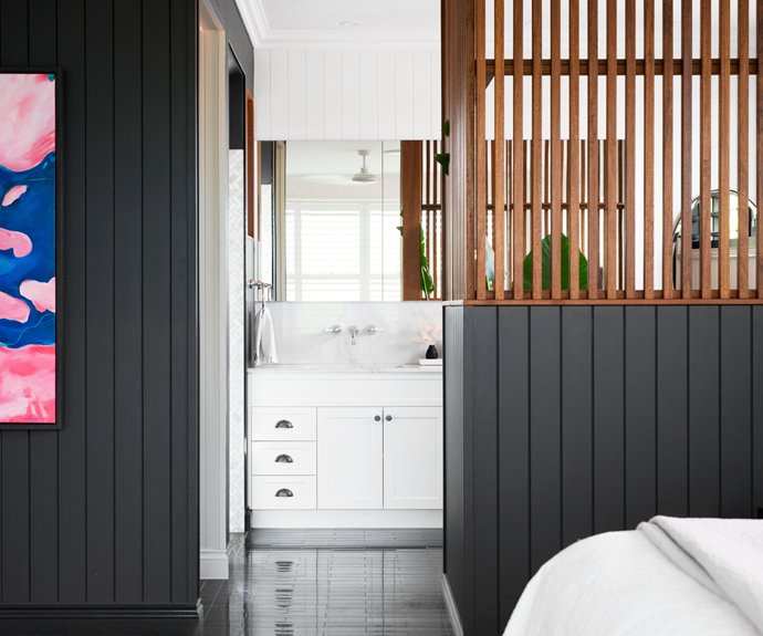 A VJ wall in Dulux Black Caviar teamed with timber battens defines the large ensuite in the main bedroom and provides the ideal backdrop for a Rachel Prince artwork, titled 'Afterglow'.