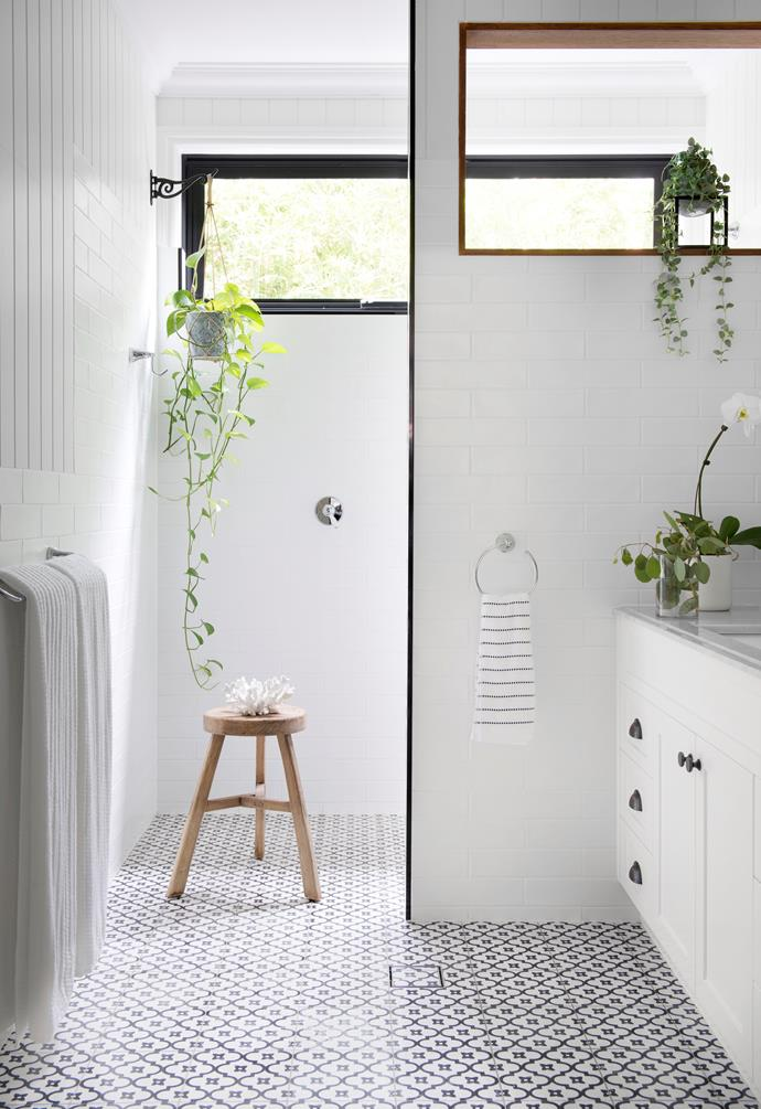 This light-infused guest bathroom embraces the home's classic black and white palette, with textural surfaces creating layers of interest. Continuing the same joinery from the kitchen, the vanity features Carrara marble, 2-pac cabinetry and Dulux Lexicon Quarter on the VJ walls. White subway tiles from The Tile Mob help bounce light around the room, which is further enhanced by a wall cut-out designed to capture garden views. A stool from Magnolia Interiors, in the shower zone, provides a moveable platform for display.