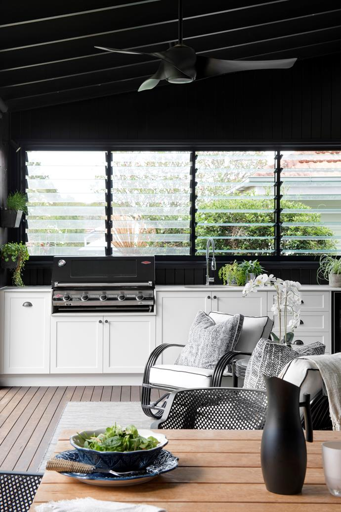 """""""To create an intimate feel here, the walls and ceiling were painted black, which also provides crisp contrast to white cabinetry housing a full outdoor kitchen and Beef Eater barbecue. """"It took us a long time to find the perfect black, the paint we tested either had a blue tinge, or just wasn't black enough,"""" explains Justine, who finally chose Resene Black. Cane chairs teamed with Coca Mojo cushions are the perfect place to kick back after lunch and relax."""