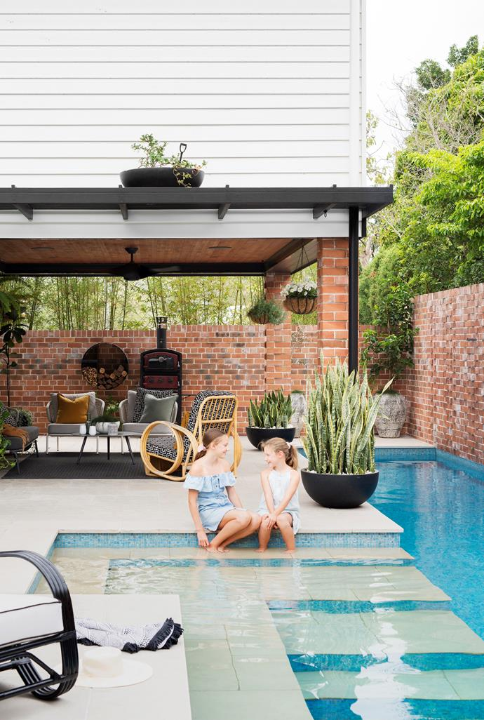 """A favourite spot for the family is the well-appointed Cabana overlooking the pool. """"The kids are in and out of the water all day long and I find it really relaxing to be out there,"""" says Justine. """"We often cook and eat outside in the cabana. We regularly have friends or family over for a swim and dinner and it's so easy to entertain with the pizza oven and outdoor kitchen."""" Furnished with pieces from Coco Republic and a second-hand Pretzel chair, reupholstered in Warwick Outdoor fabric, the neutral scheme, grounded with Eco Outdoor 'Garonne' limestone pavers, makes the surrounding red bricks and plants pop. For a similar Pretzel-style chair try Naturally Cane. And the pizza oven and wood holder? They're from Bunnings"""