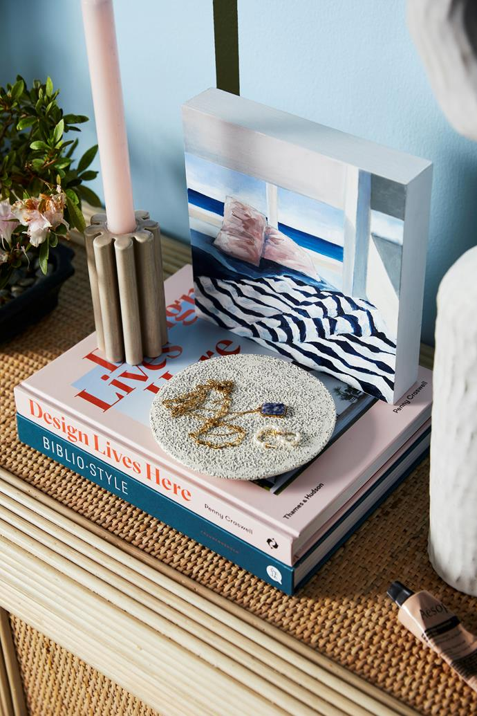 Andrej Urem 'Crux' candle, $70, Makers Mrkt. Mima vase in Natural, $79.95, Kas. Aeyre 'Prima' candlestick, $129, Reliquia Collective. Books from Kinokuniya. Candle and candle holder, stylist's own. The Invitation artwork by Liss Finney, $500, Saint Cloche. Vanity organic display plate, $155, Marloe Marloe. Floria necklace, $149, Reliquia Collective. Alex hoops, $129, Reliquia Collective. Asymmetry vessel by Kerryn Levy, $1200, Curatorial+Co. Resurrection Aromatique hand balm, $33 for 75ml, Aesop.