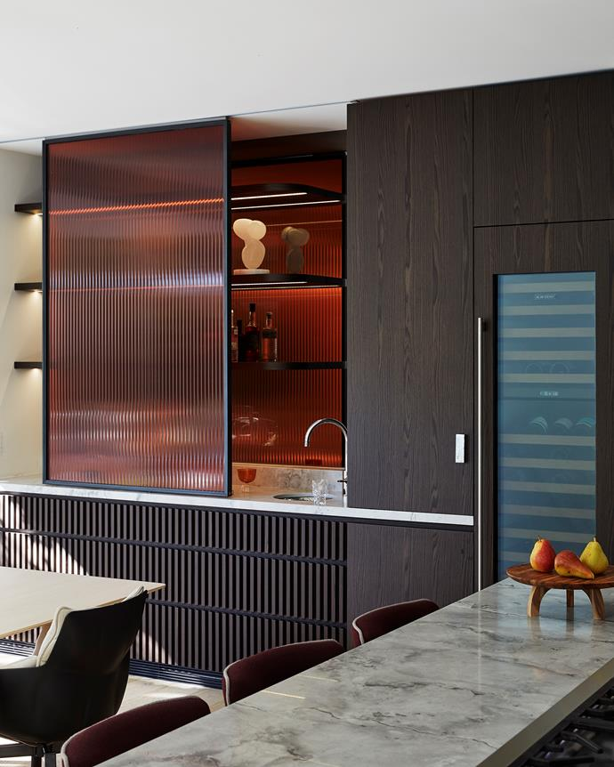 The sophisticated bar area , featuring Eveneer 'Even Charred' veneer joinery, custom amber broadline glass and a Sub-Zero wine fridge, is the focal point in the open-plan space.