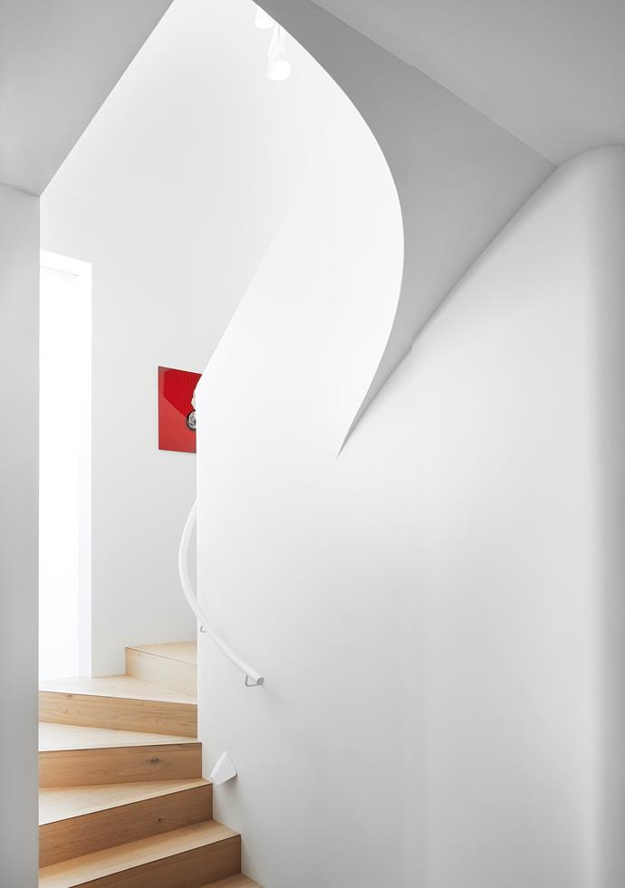 """Clean curves carry through from the home's ceilings to the staircase. """"It's sculptural without stealing the show,"""" says Sara. Artwork, artist unknown."""