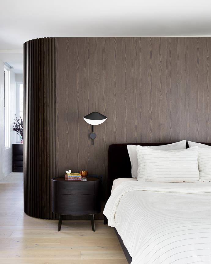 The custom dividing wall, a Studio George creation, separates the main bedroom from the bathroom and walk-in wardrobe. Kelly bed and night table, Poliform. Bedlinen, Cultiver. Serge Mouille wall light, Cult.
