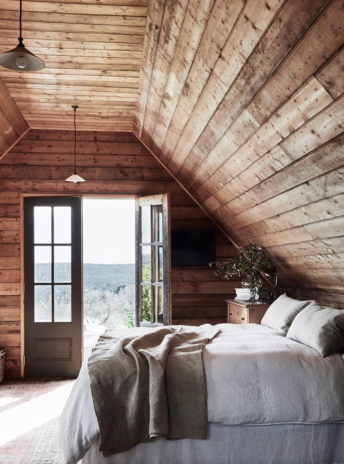 Helen and Rodney's bedroom was built in the steep gabled roof space of the cottage. Antique French doors were installed instead of windows to make the most of the sweeping view over the treetops in Wombat State Forest.