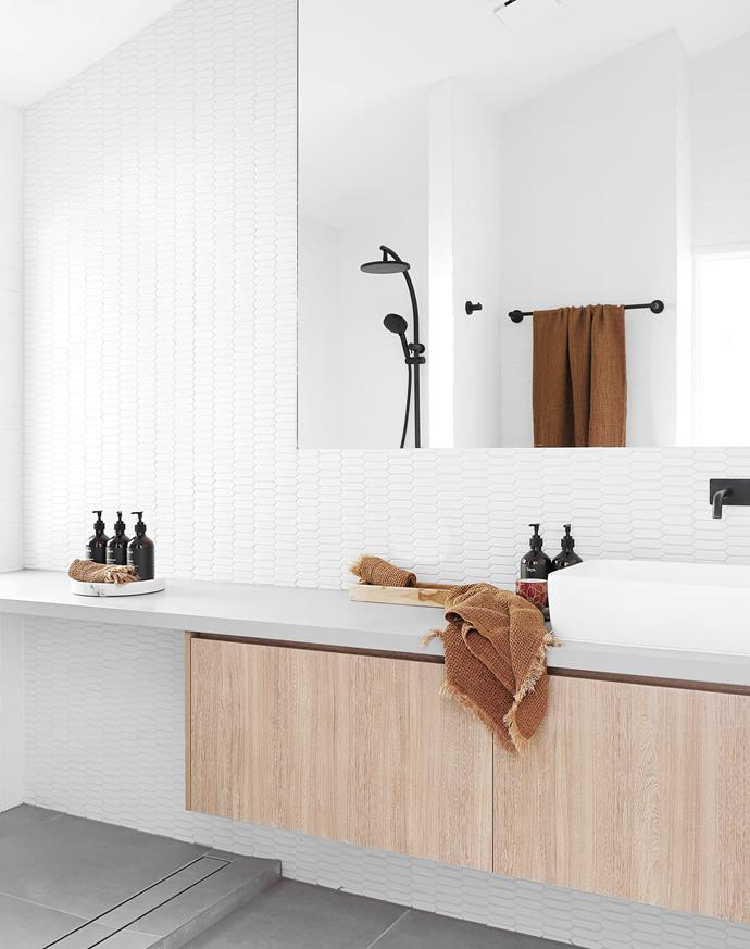 Wall and floor tiles, all Ace Stone+Tiles. Tapware and basin, all Phoenix Tapware. Essastone benchtop in Taupe Concrete. Laminex vanity in Honey Elm Riven.