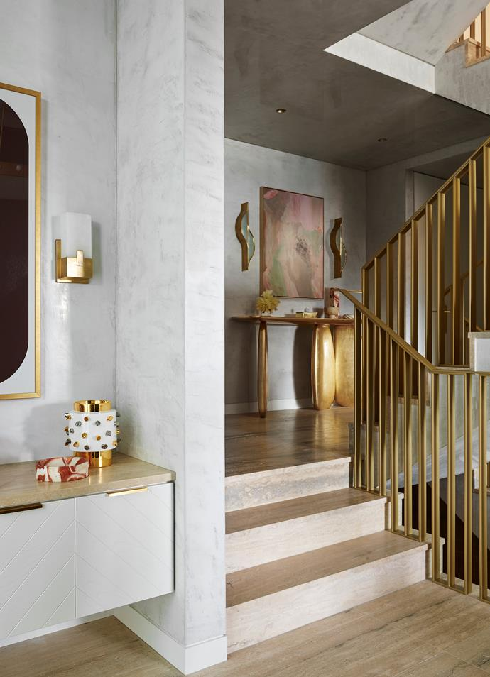 The glamorous staircase features custom brass railings with Silver Travertine from Worldstone underfoot. To the left is a print by Greg Natale titled Emilio, which hangs above a custom console by the designer. Softly by Annie Everingham is displayed on the landing above an 'Ardara' console in gold leaf from Brabbu.