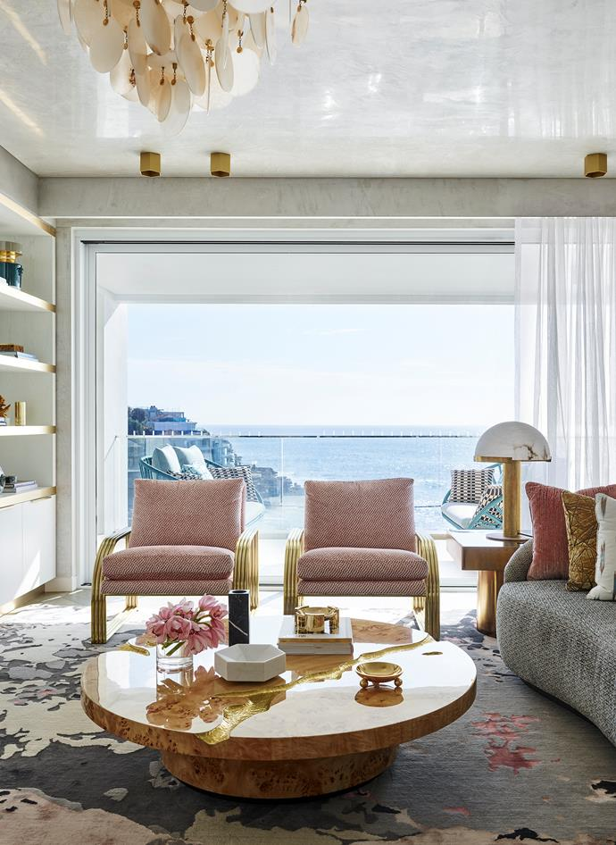 A pair of 'Reynolds' chairs by Milo Baughman and a 'Turner' sofa from Arteriors face an 'Empire' centre table from Boca do Lobo topped with Greg Natale accessories, all on an 'Onyx' rug by Greg Natale from Designer Rugs. 'Villiers' matt-gold side table from Regency Distribution and Kelly Wearstler 'Melange' table lamp. Elte stone-disc chandelier from LightCo and 'Hexo' spotlights from Est Lighting