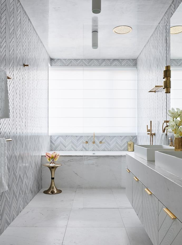 Walls are clad in Lava Stone and Snow Pyramid chevron marble tiles from Worldstone as are the Artemis marble tiles used for the floors. Gilded elements include a 'Botti' side table from Essential Home and CTO Lighting 'Ring' wall light from Spence & Lyda.