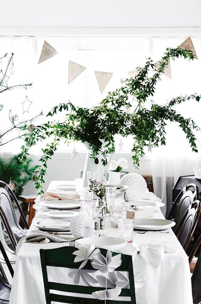 If you're short on space and need to use the limited room to host a fabulous Christmas dinner, just great a large greenery display in a vase and hang your baubles from it's branches! For extra points, top with a sparkly star so no one will wonder where the Christmas tree is. Photographer: Lisa Cohen