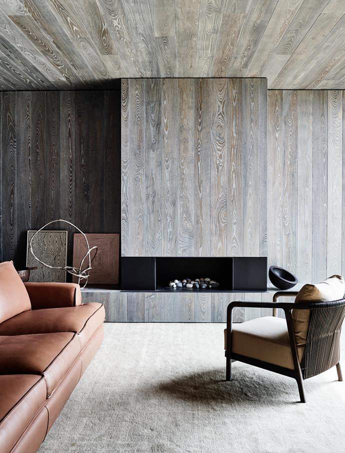 In the library the walls and ceiling are clad in custom-stained crown-cut American ash and the floor is covered in a carpet from RC+D. The Flexform 'Crono' armchair and the Fanuli 'Keely' sofa in natural saddle leather, both from Fanuli, are positioned around the 'Simplicity 1000' gas fireplace from Real Flame. Bronze sculpture by Camie Lyons and artworks by Warlimpirrnga Tjapaltjarri from Scott Livesey Galleries.