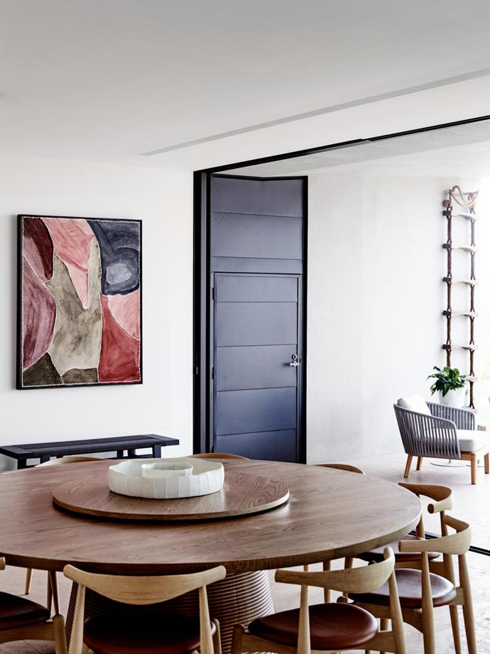 The dining room which links to the outdoor pool terrace is enriched by Lilly Creek Waterhole, an artwork by Churchill Cann. Home Hotel black elm bench from Poliform. Custom 'Butterworth' table from Lowe Furniture with lazy susan from Hub. Carl Hansen 'Elbow' chair from Cult.