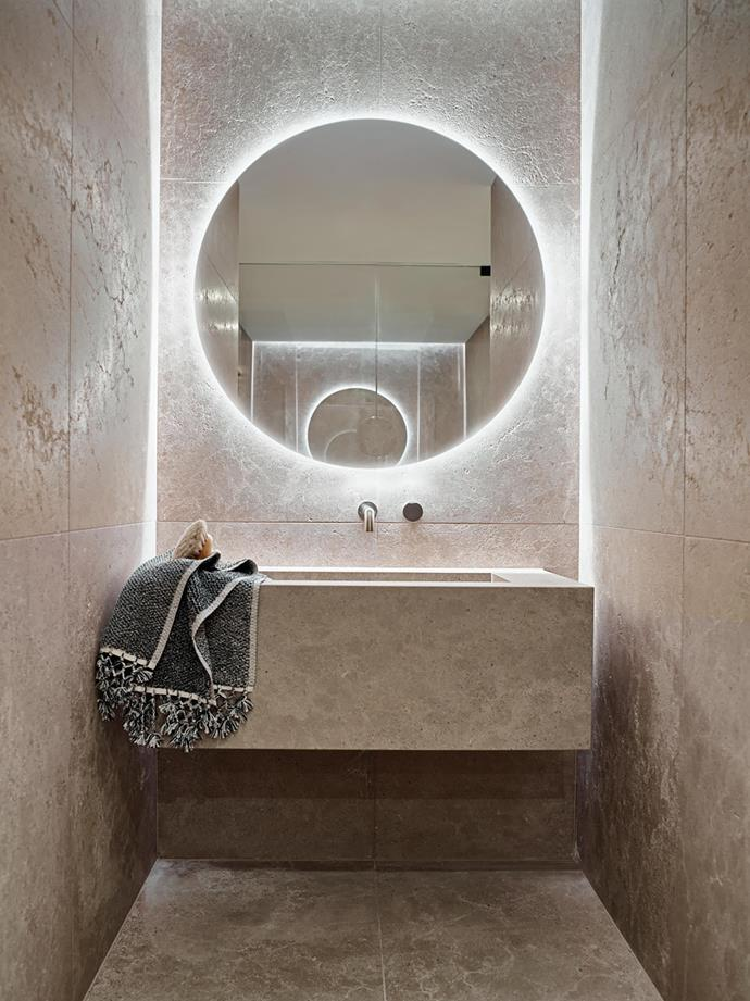 The powder room with custom vanity and mirror in the wellness retreat makes the most of the luminous quality and delicate veining of Cristallo quartzite. Towel from Loom Towels.