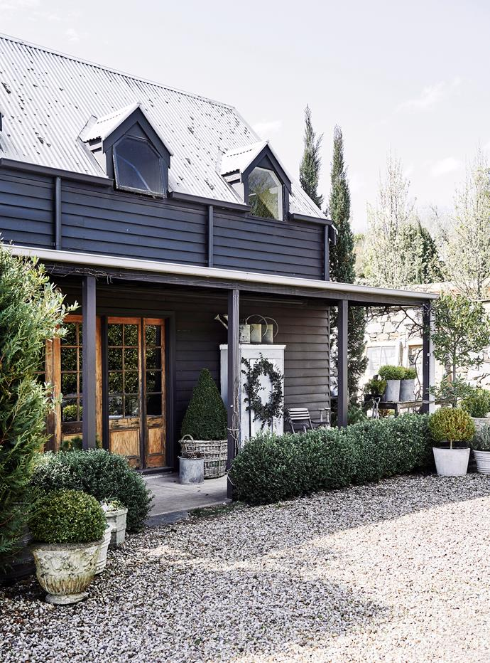 """A clipped box Christmas tree sits in an old grape harvesting basket on the verandah of this [timber cottage in Daylesford](https://www.homestolove.com.au/timber-cottage-gable-roof-21950