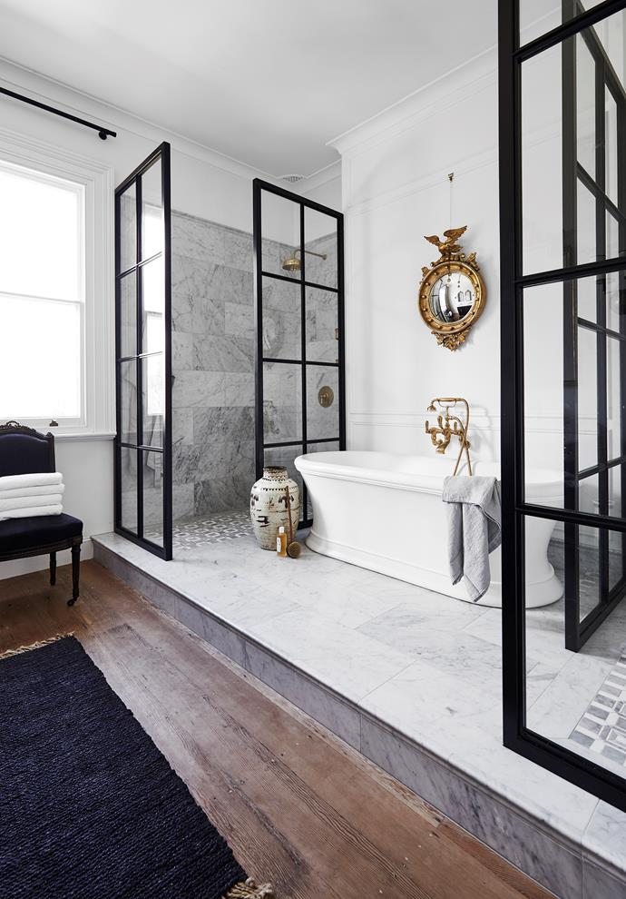 """Timber flooring in a bathroom may be a controversial choice, but at his [country home in Central NSW](https://www.homestolove.com.au/stylist-steve-cordonys-chic-country-home-22083 target=""""_blank""""), stylist Steve Cordony has used the combination of Oregon floorboards and Carrara marble tiles to delineate the room's bathing and dressing zones. """"The showers contrast with the soft lines of the bath and provide another interplay between contemporary and traditional,"""" says Steve."""