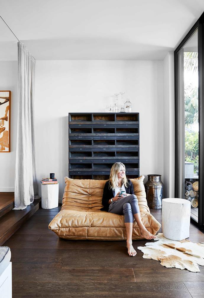 "**Rumpus room** Sarah chilling out 'downstairs' on her favourite chair, an iconic Ligne Roset 'Togo' sofa in leather. The shelving unit behind her is a set of vintage mailing holes bought some time ago. Tonk timber stools in White, [MCM House](https://www.mcmhouse.com/|target=""_blank""