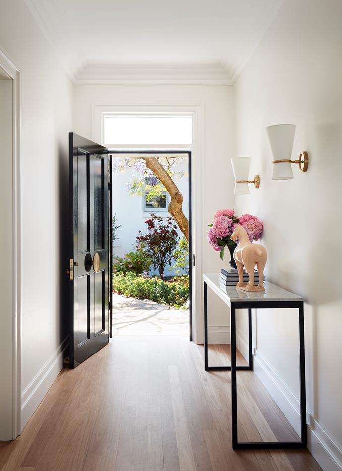 A pair of Visual Comfort 'Clarkson' pivoting wall sconces in brass with linen shades by Aerin from Montauk Lighting Co illuminate the entrance where the door is finished with a brass handle from Designer Doorware. The existing solid-timber floor was resurfaced and finished in a matt whitewash.