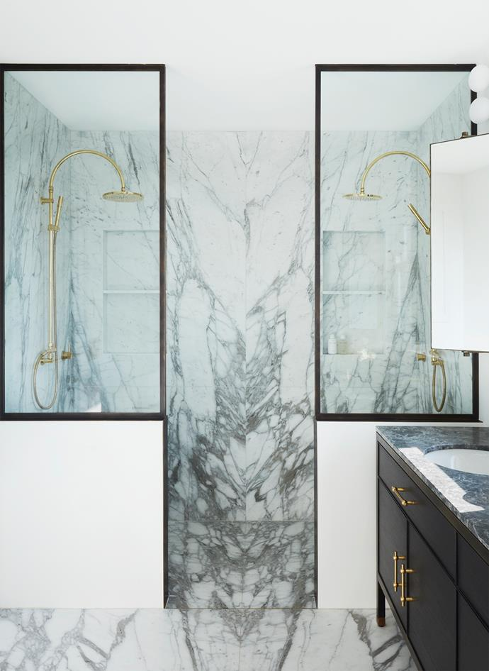 Striking bookmatched Calacatta Vagli marble features on the shower walls and floor with the custom vanity clad in Nero Marquina marble, crown-cut American oak veneer and blackened brass frame. Brodware 'City Plus' brass 