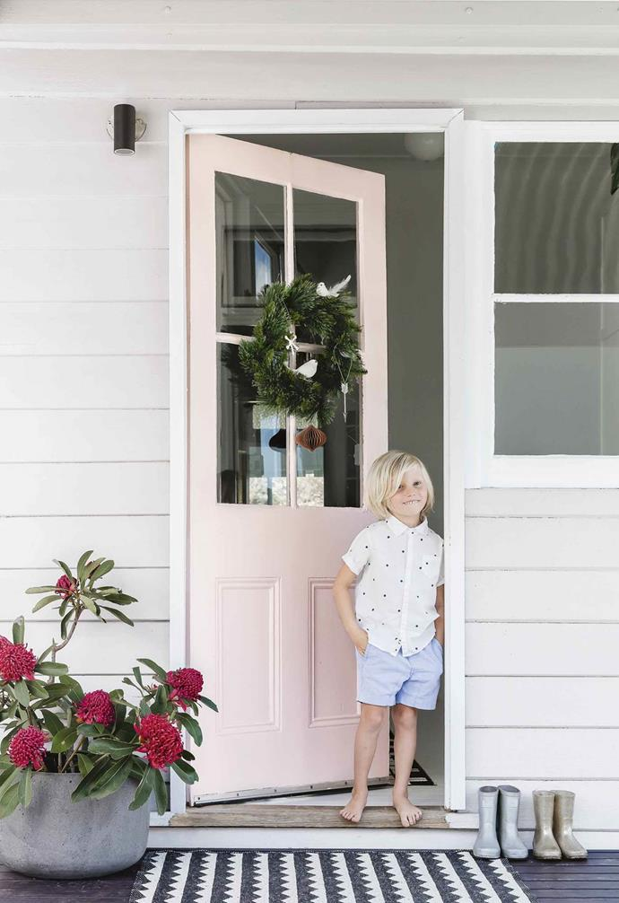 "In this renovated [coastal farmhouse](https://www.homestolove.com.au/coastal-farmhouse-thirroul-17691|target=""_blank"") a pastel pink door adds a bright pop of colour to the entryway. For the festive season a simple wreath hangs on the door, and a pot full of waratah flowers adds a native twist on the traditional Christmas palette."