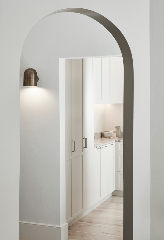 From the entrance hallway, which boasts a Duomo sconce, you can enter the bathroom, kitchen and living room. The arch was painted in Porter's Paints 'French Blue' to highlight the stunning original feature.