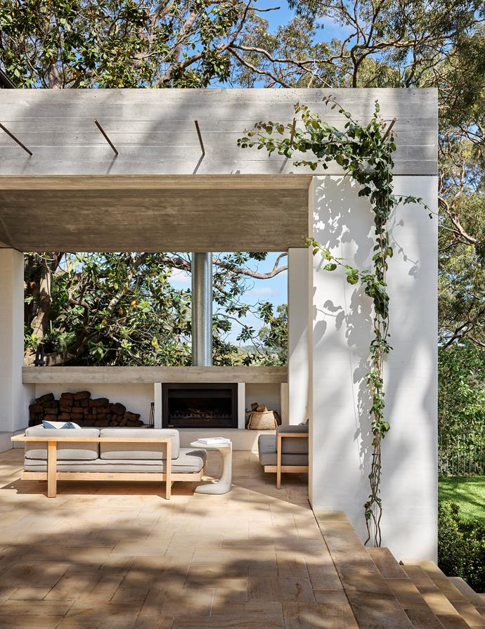 Bougainvillea drapes a column in the new garden room with a wood-burning Jetmaster fireplace. Tribù 'Pure' outdoor sofas from Cosh Living and 'Font' side table from Fanuli.
