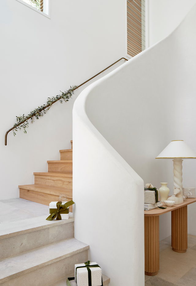 "For a modern interpretation of the traditionally bright and bold garland, wind strands of delicate foliage (olive branches look lovely) around handrails (as seen in this [coastal home](https://www.homestolove.com.au/casual-christmas-decorating-ideas-22082|target=""_blank"")) or curtain rods."