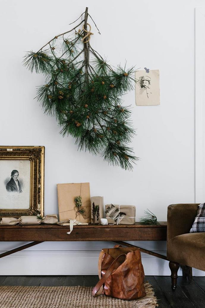 If you adore the smell of pine but don't have the space for large tree, consider hanging a fragrant pine-tree branch on a blank wall, upside-down or not, hang some light baubles or ribbons on it and pile up the presents underneath to create the perfect mini Christmas tree!