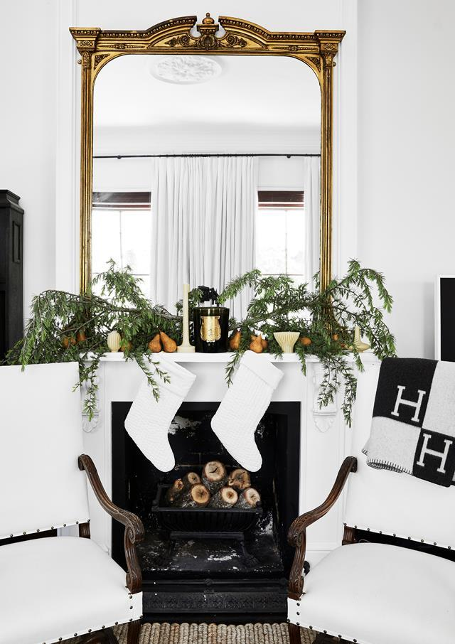 "A simple colour scheme works marvellously in this elegant living room [styled by Steve Cordony](https://www.homestolove.com.au/stylist-steve-cordonys-chic-country-home-22083|target=""_blank""). A pair of white Christmas stockings and greenery look sophisticated on the fireplace mantel."