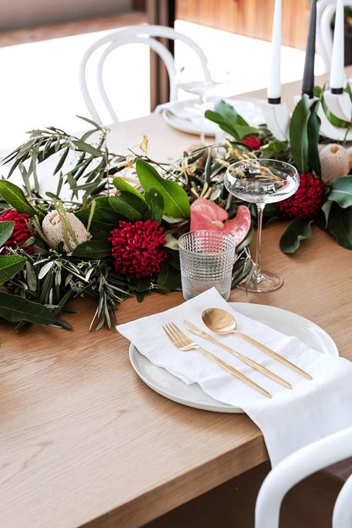 Interweaving banksia, waratah, protea, olive leaf, aranthera and anthurium along the centre of this festive table makes a sweet-scented alternative to a textile runner.