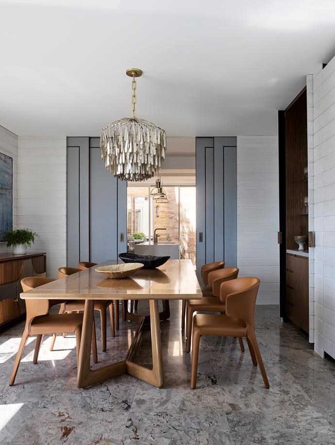 The generous dining room now comfortably seats 10. Gregorius Pineo 'Hansen' dining table in bleached walnut from Kneedler Fauchère, LA. 'Husk' wrap-around dining chairs from Zuster. Philip Nimmo 'Montage' sideboard and Fisher Weisman 'Gilded Cage' round chandelier, both from Jean de Merry, LA. Platters on dining table from Studio Levine.