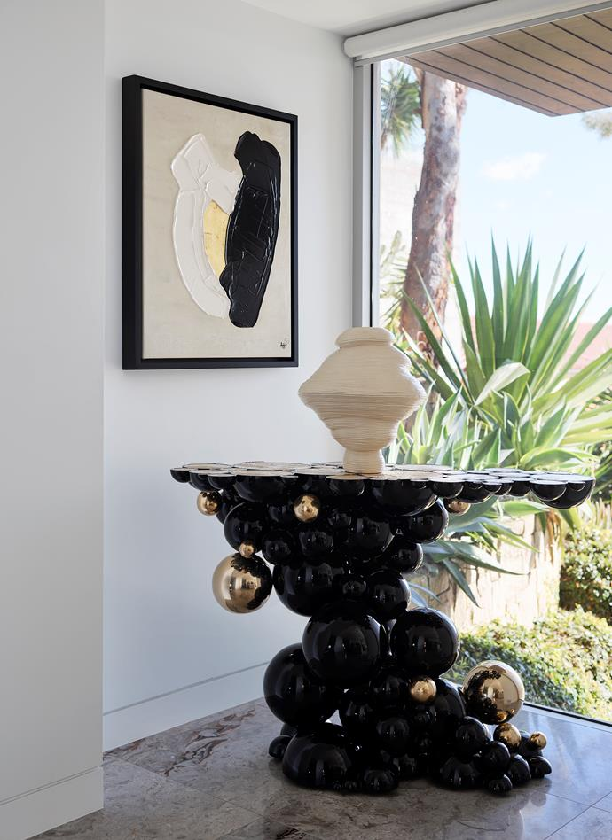 'Newton' console in black lacquered aluminium and gold-plated brass from Boca Do Lobo, Portugal. *Keep the Earth Clean, It's Not Uranus* sculpture by Zhu Ohmu in glazed ceramic from Gallery Sally Dan-Cuthbert. *Between* mixed-media artwork by Aude Herledan from Kneedler Fauchère, LA.