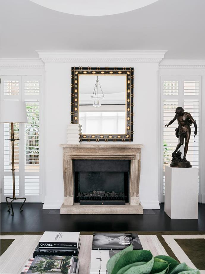 """A striking stone fireplace is the focal point of the living room in this [classic Sydney home](https://www.homestolove.com.au/a-classic-sydney-home-decorated-with-contemporary-and-antique-pieces-20209