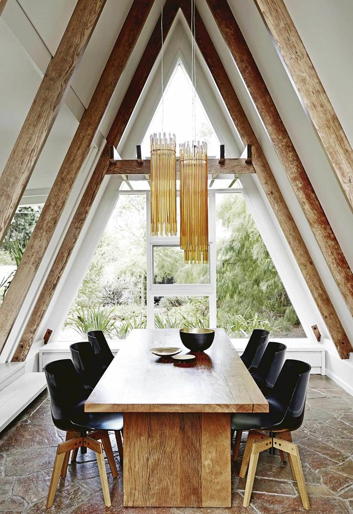 "Set in this renovated [heritage home's](https://www.homestolove.com.au/a-frame-house-melbourne-18748|target=""_blank"") unique A-frame, this dining space features the original stone floor. The owner made a model of the lights – Vistosi 'Diadema' pendant lamps imported from Italy – from paper and chopsticks to ensure they were hung at exactly the right height. A Mark Tuckey table is teamed with MDF Italia 'Flow' chairs from Hub Furniture."