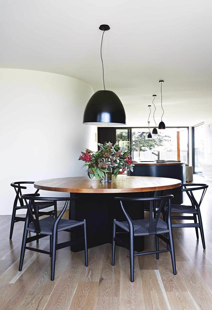 "Black chairs and large pendant lights provide a striking contrast to the light wood floors in the dining zone in this [contemporary beach house](https://www.homestolove.com.au/modern-rammed-earth-beach-house-17299|target=""_blank"") retreat. The black dining chairs and dark base of the timber-topped dining table echo the design of the statement kitchen island."