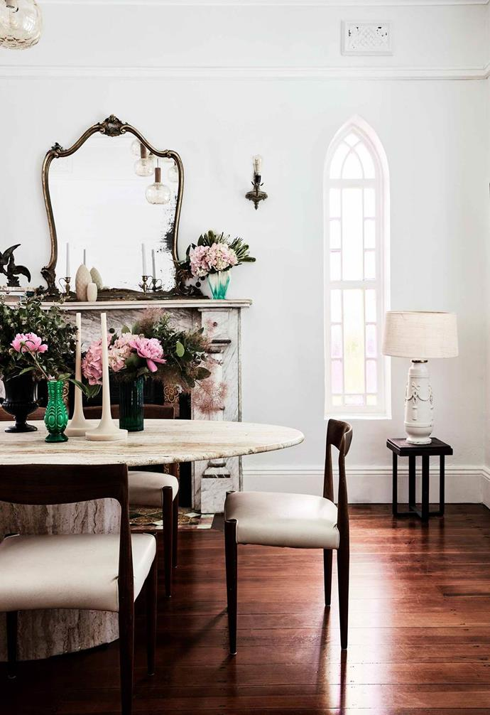 "An oval travertine table is the hero of the dining room in this [Italianate Victorian home](https://www.homestolove.com.au/italianate-victorian-home-19959|target=""_blank""), creating a dramatic contrast to the dark timber flooring. A well-placed mirror on the fireplace mantle maximises the natural light within the room."