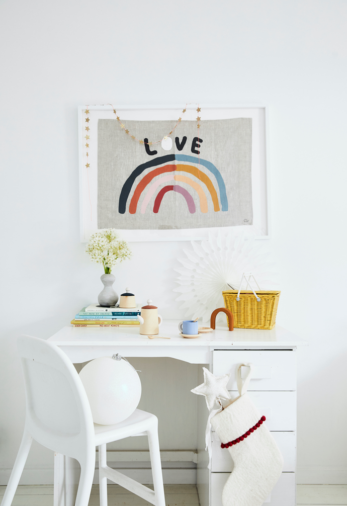 Sophie salvaged the desk from the side of the road and gave it a fresh coat of white paint. The chair is Ikea, the rainbow artwork is by Rachel Castle and the basket is Olli Ella.