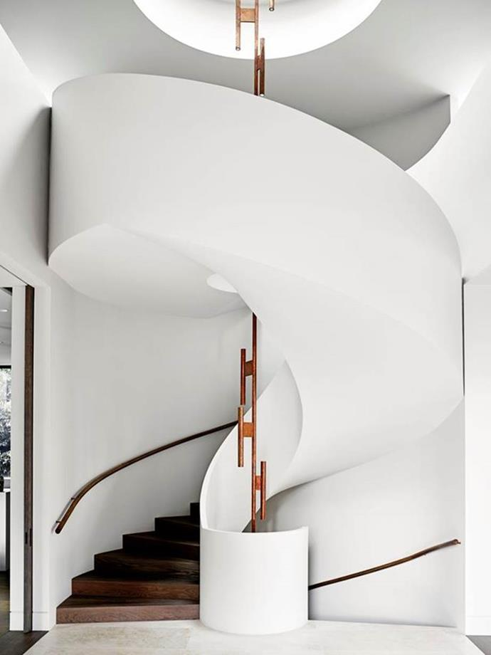 """Architect Rob Mills's signature wraparound staircase makes a grand statement in the entryway of this [luxurious home designed with entertaining in mind](https://www.homestolove.com.au/luxurious-home-designed-with-entertaining-in-mind-6733