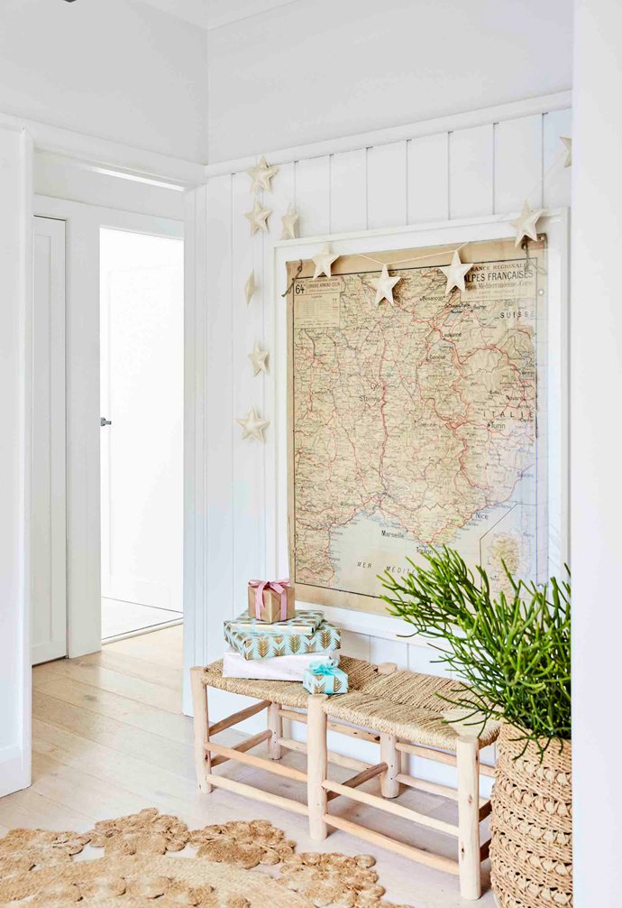 A star garland from Honeybee Homewares follows the neutral yet inviting scene at the home's entry, created by a vintage map found in France, an Armadillo & Co rug and a bench seat from Home On Darley.
